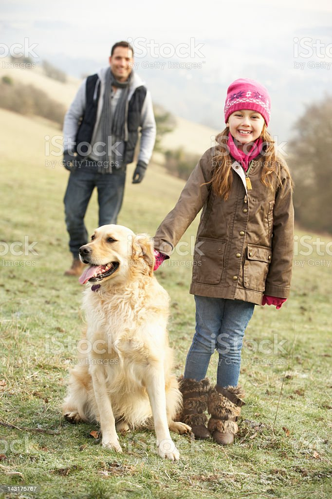 Father and daughter walking dog in country royalty-free stock photo
