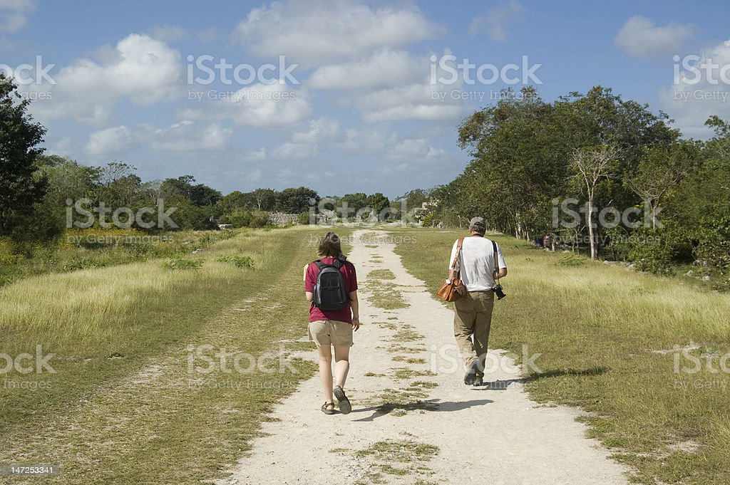 Father and daughter walking down a worn road royalty-free stock photo