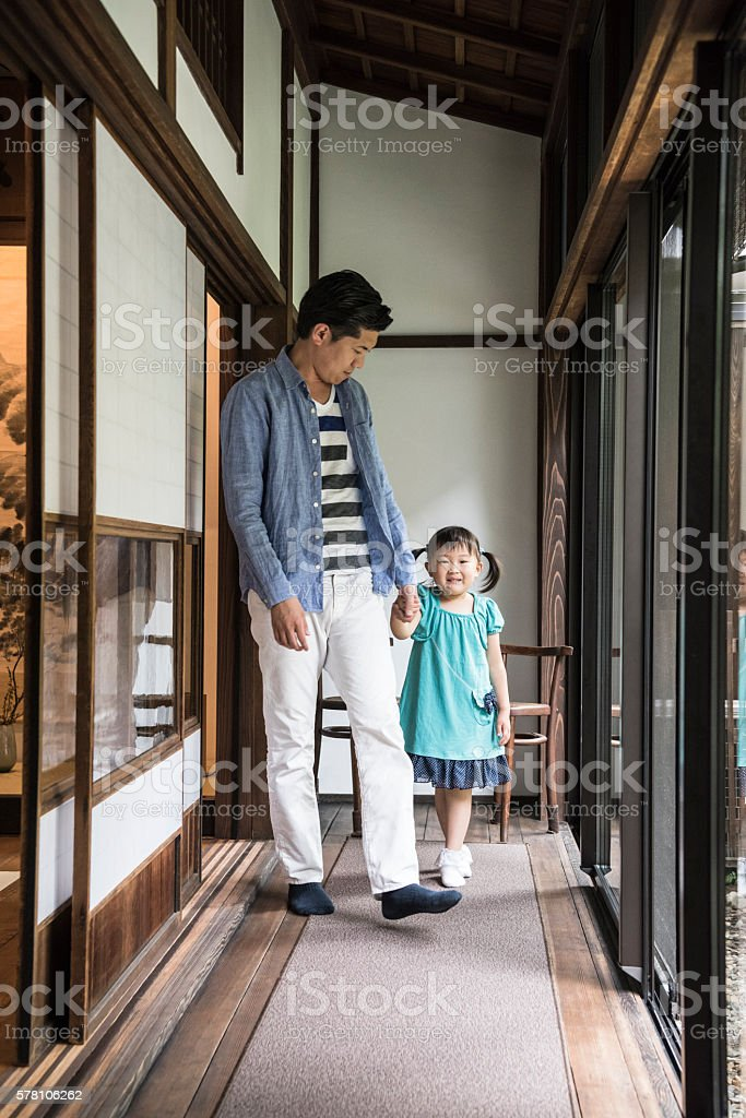 Father and daughter walking down hallway stock photo