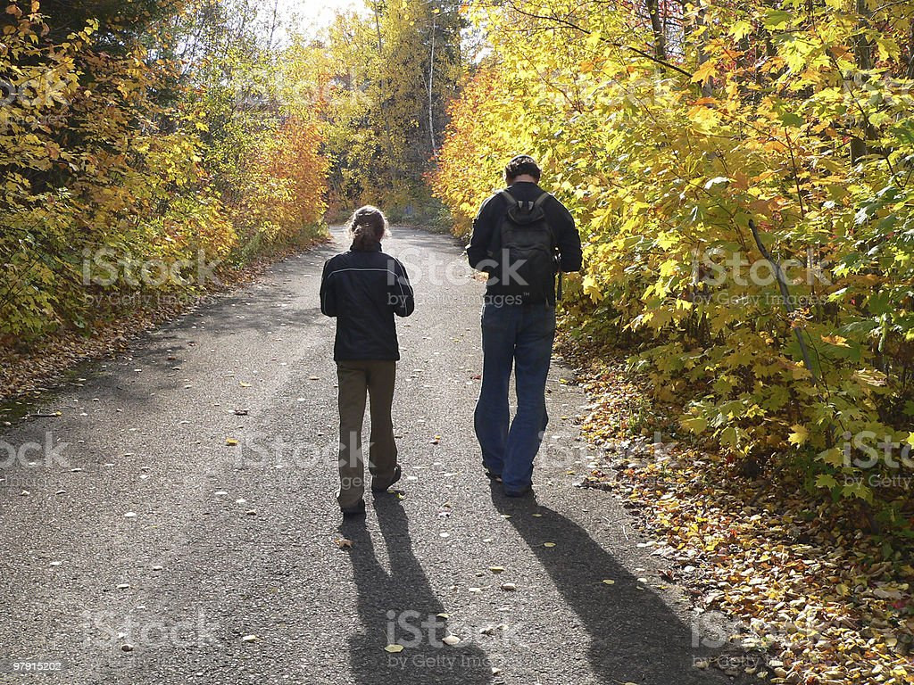 Father and daughter walking in woods stock photo