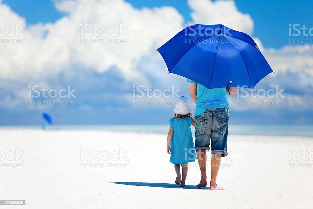 Father and daughter walking on a beach with a blue umbrella stock photo