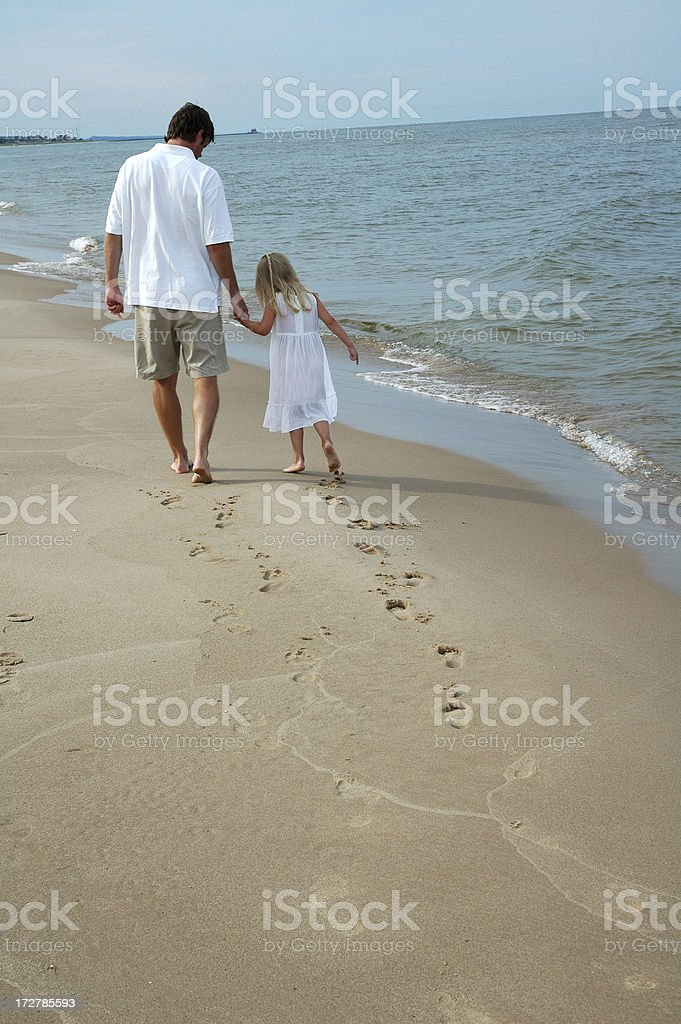 Father and Daughter walking on beach royalty-free stock photo