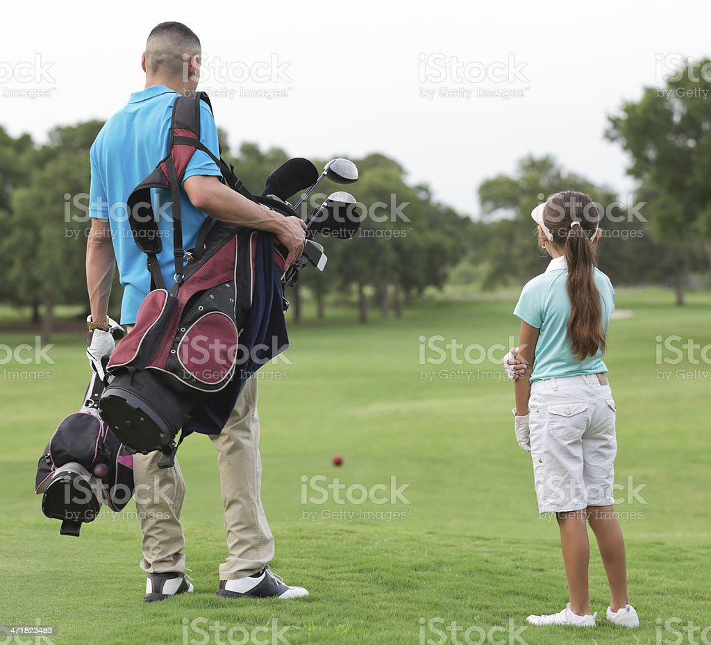 Father and daughter walking on course while playing golf together royalty-free stock photo