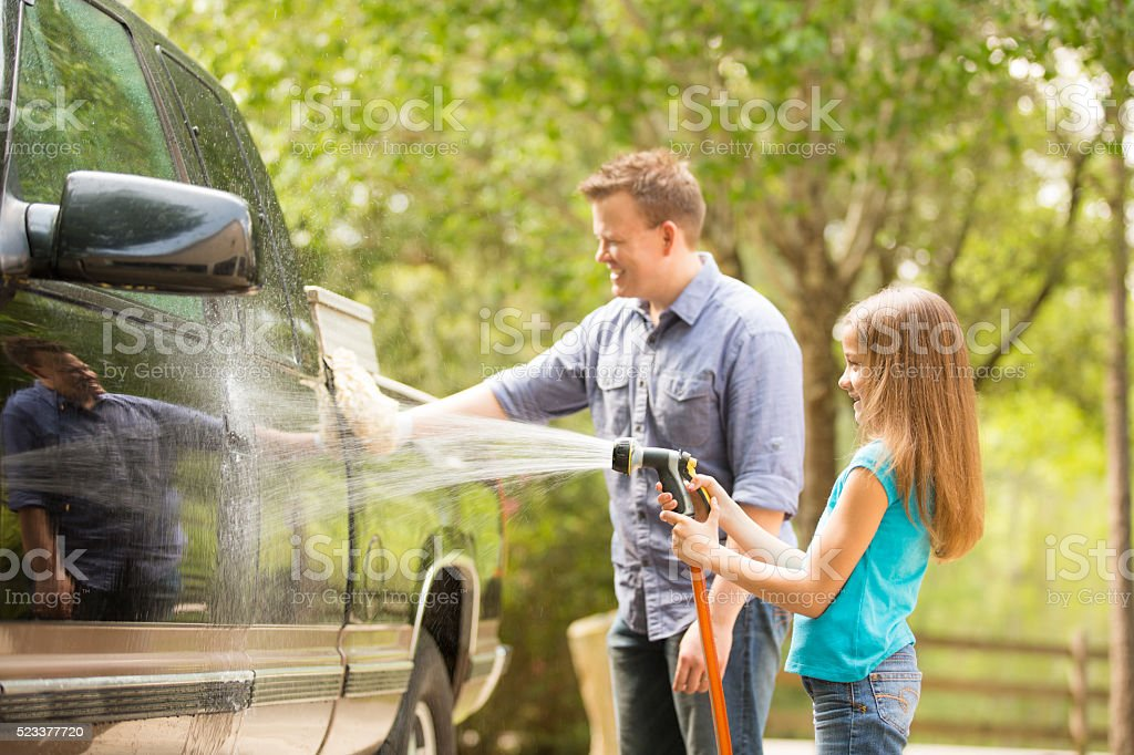 Father and daughter wash the family vehicle together outdoors. stock photo