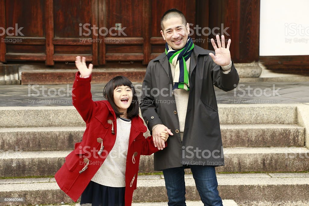Father and daughter waving hand stock photo