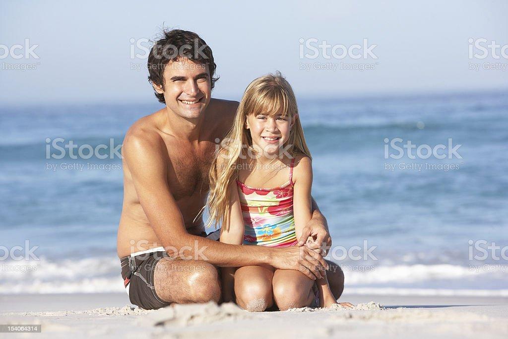 Father And Daughter Wearing Swimwear Sitting On Beach stock photo