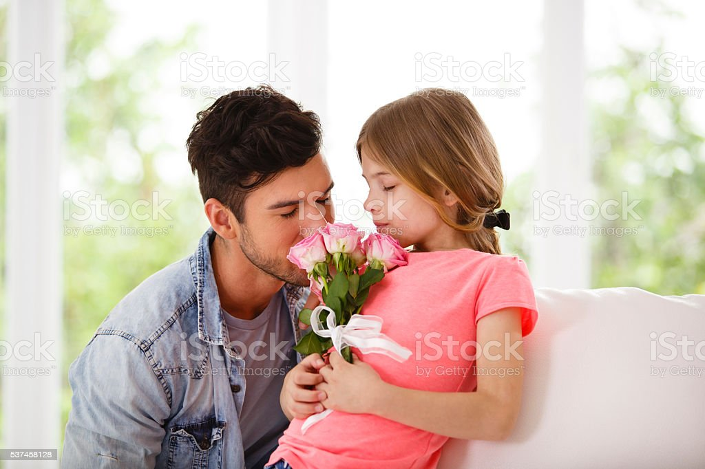 Father and daughter with bouquet of pink roses stock photo