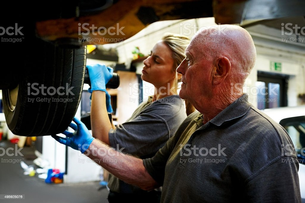 Father and daughter working together in automobile garage stock photo