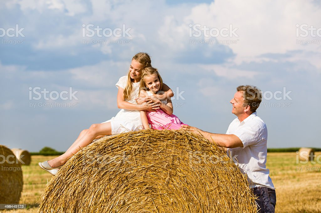 Father and daughters  by hay bale in field stock photo
