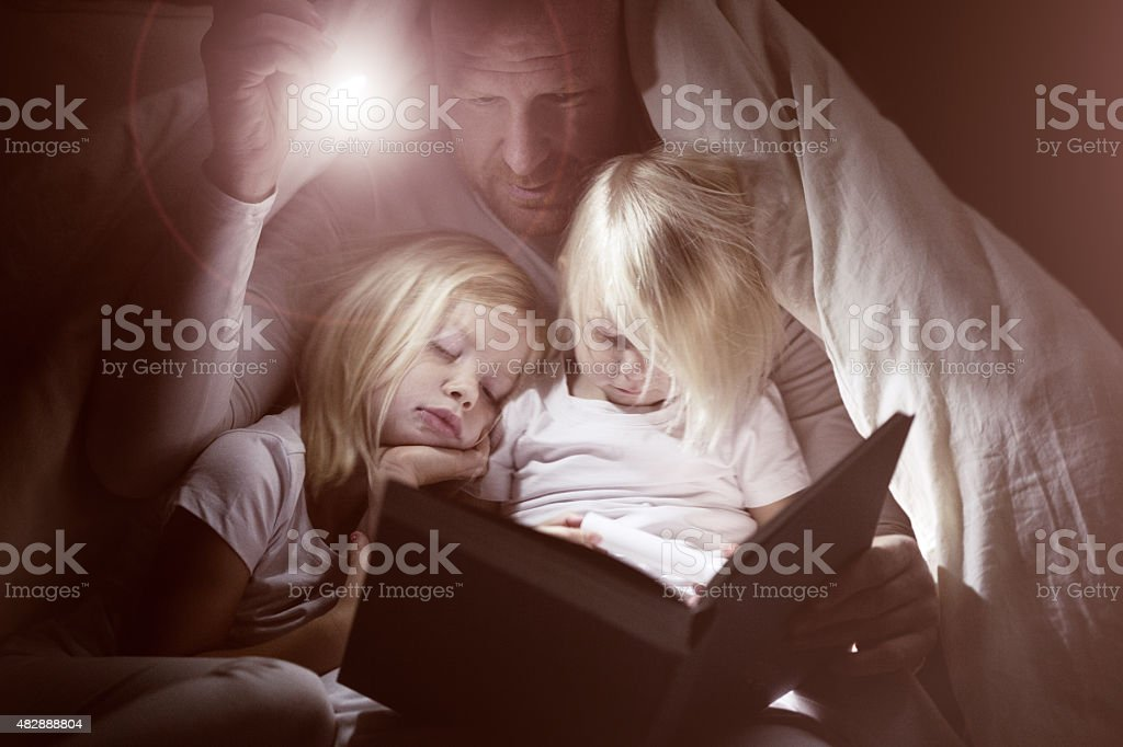 Father and daughters reading book at bedtime stock photo