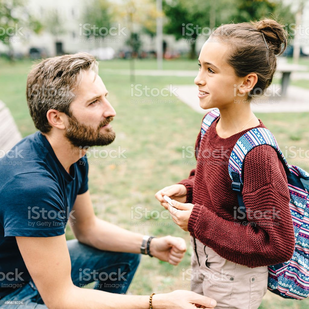 father and daughters talking after school stock photo