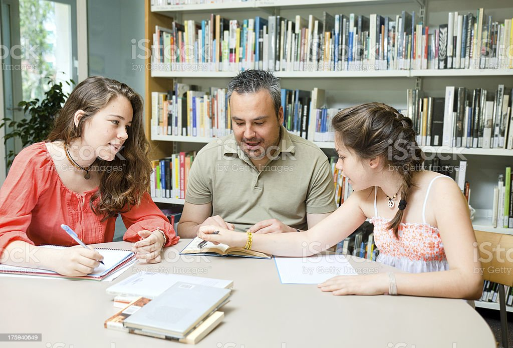 Father (or teacher) and daugthers at the public library. royalty-free stock photo