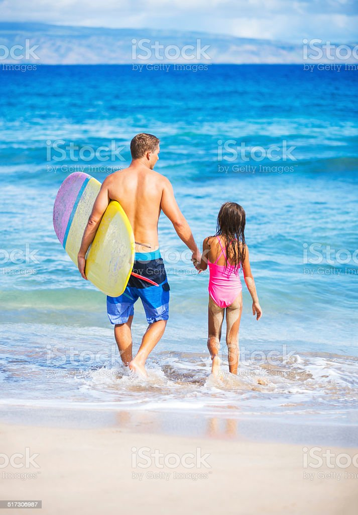 Father and Duagher on the Beach Going Surfing stock photo