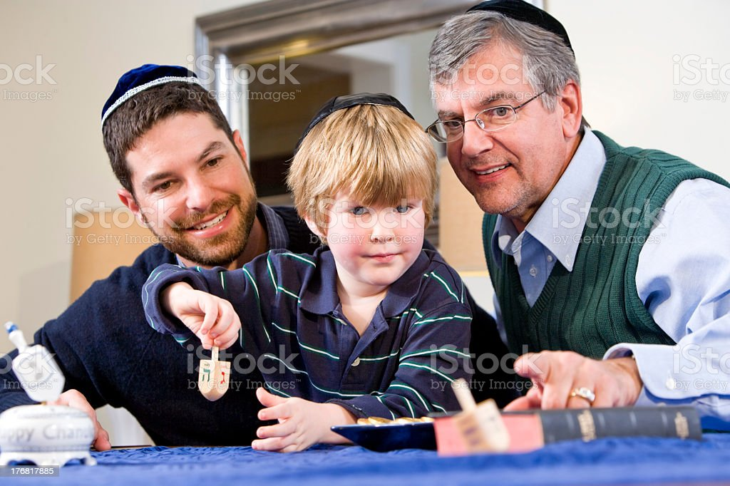 A father and grandfather teaching a boy to spin a dreidel stock photo