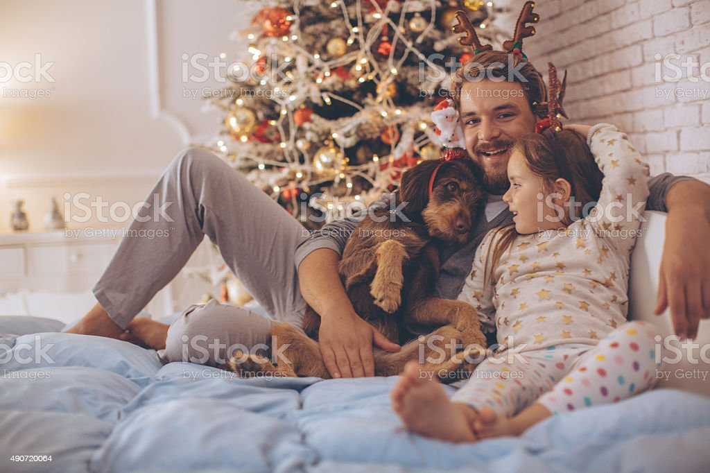 Father and his cute daughter in front of christmas three. stock photo