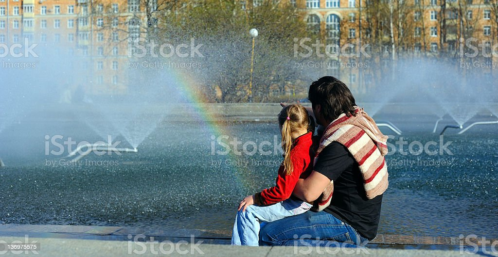 Father and his daughter looking at the rainbow royalty-free stock photo