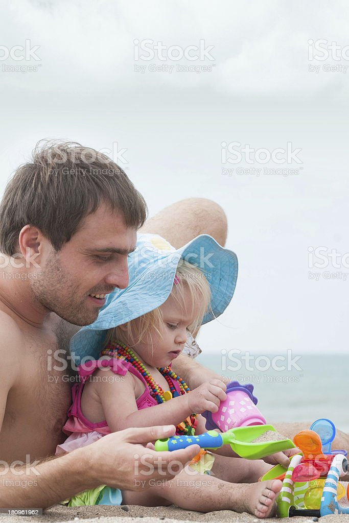 Father and his daughter playing at the beach royalty-free stock photo