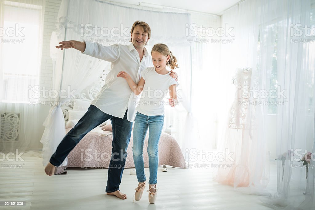 Father and his little daughter dancing at hotel room. stock photo