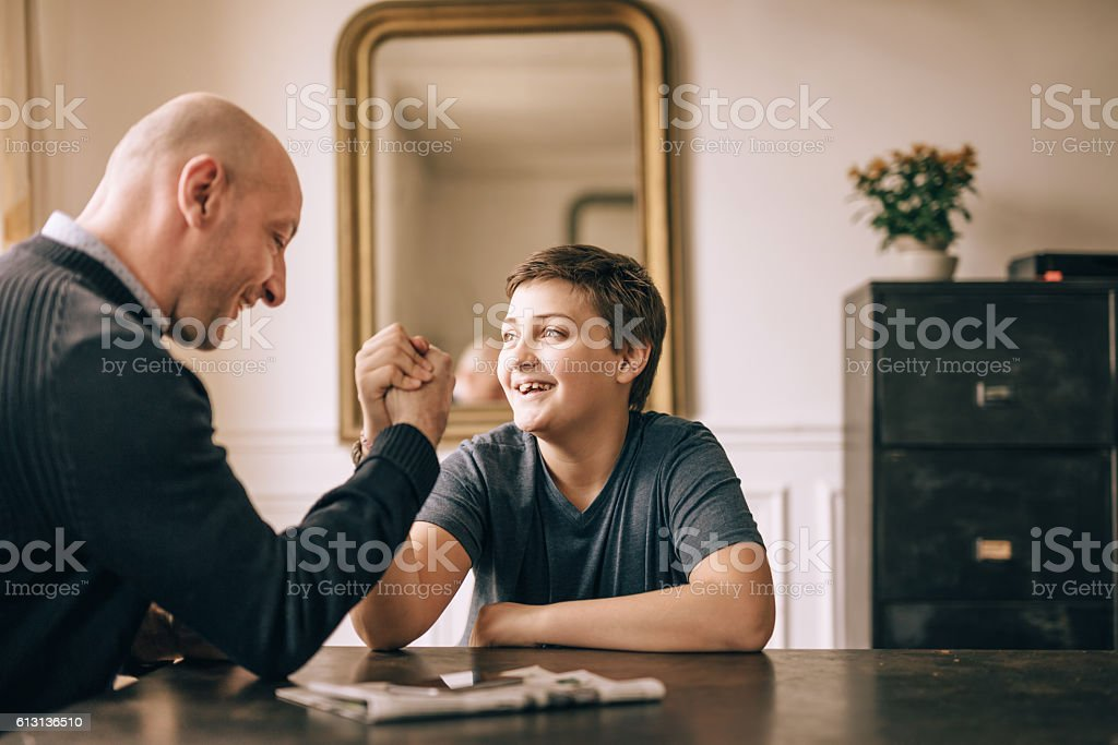 father and his son doing arm wrestling on table stock photo