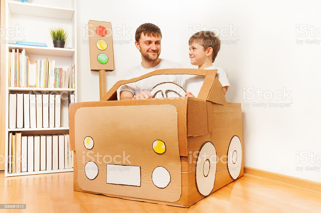 Father and his son driving handmade cardboard car stock photo