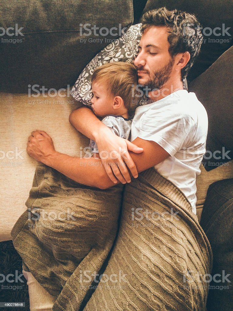 Father and his son having a nap stock photo