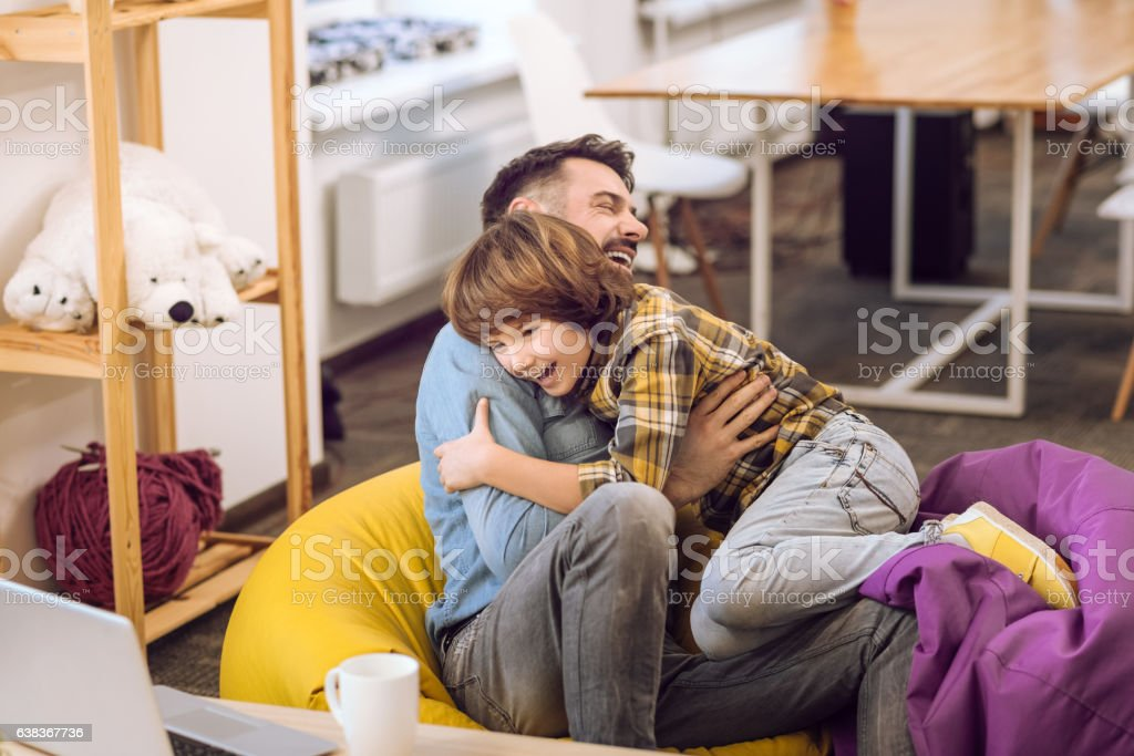 Father and his son having fun indoors stock photo