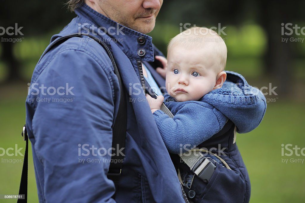 Father and his son in a baby carrier stock photo