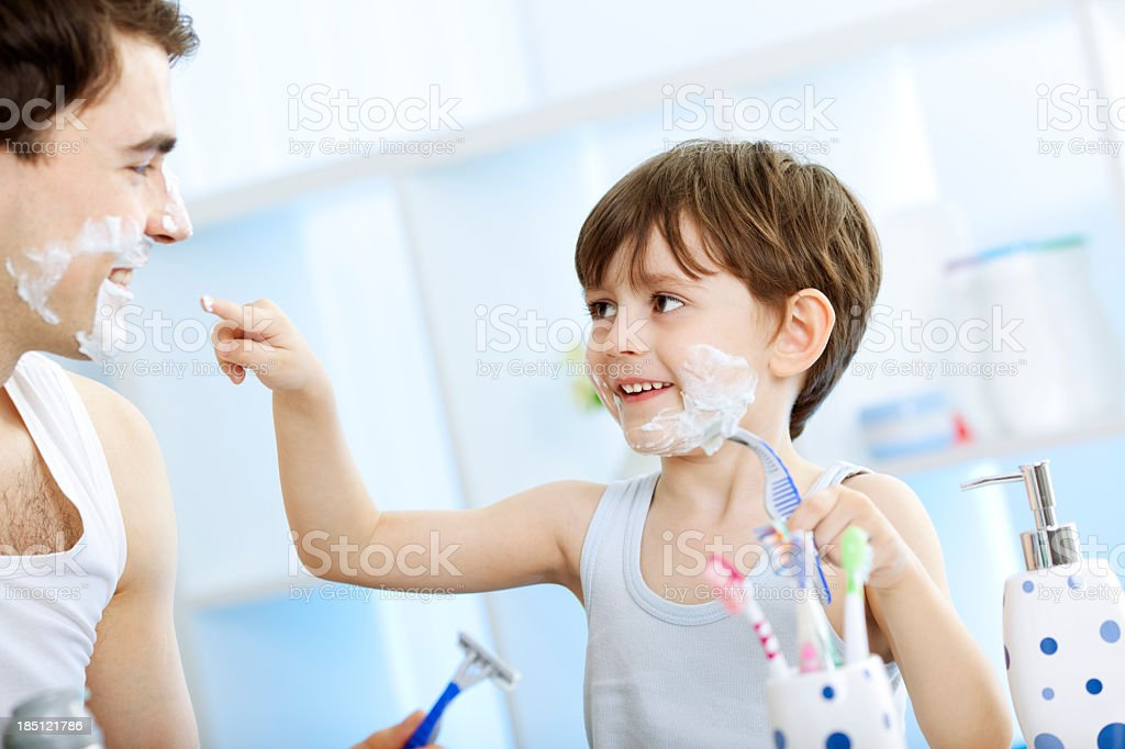 Father and his son shaving in the bathroom. royalty-free stock photo