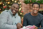 Father and His Teenage Son Opening Gifts