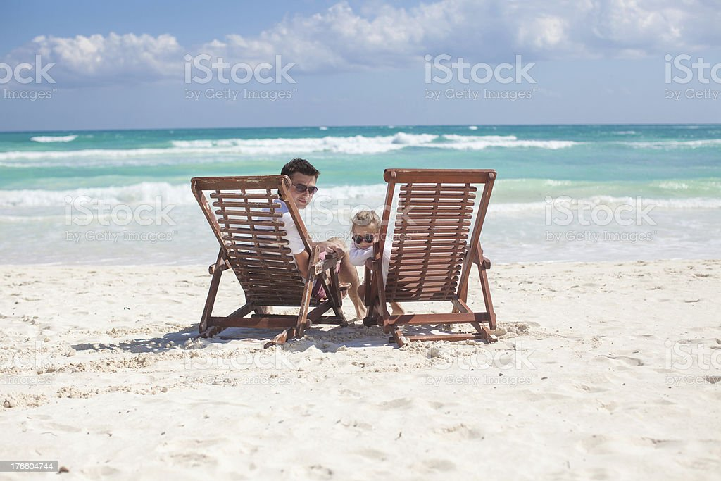 Father and his wonderful daughter sitting on beach wooden chairs royalty-free stock photo
