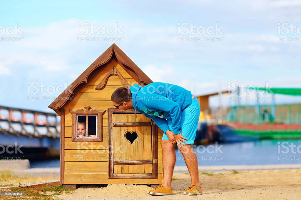 father and kid having fun in playhouse stock photo