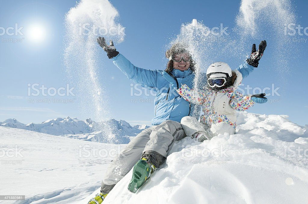 Father and kid having fun in the snow stock photo