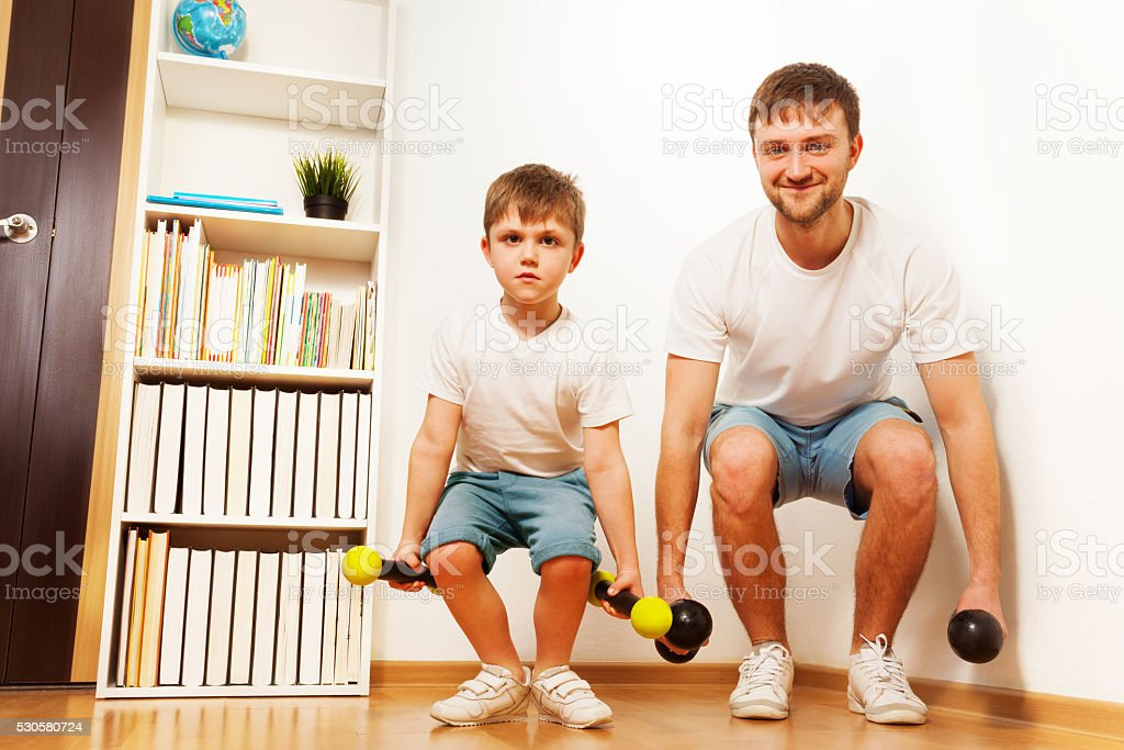 Father and kid son workout with dumbbells together stock photo