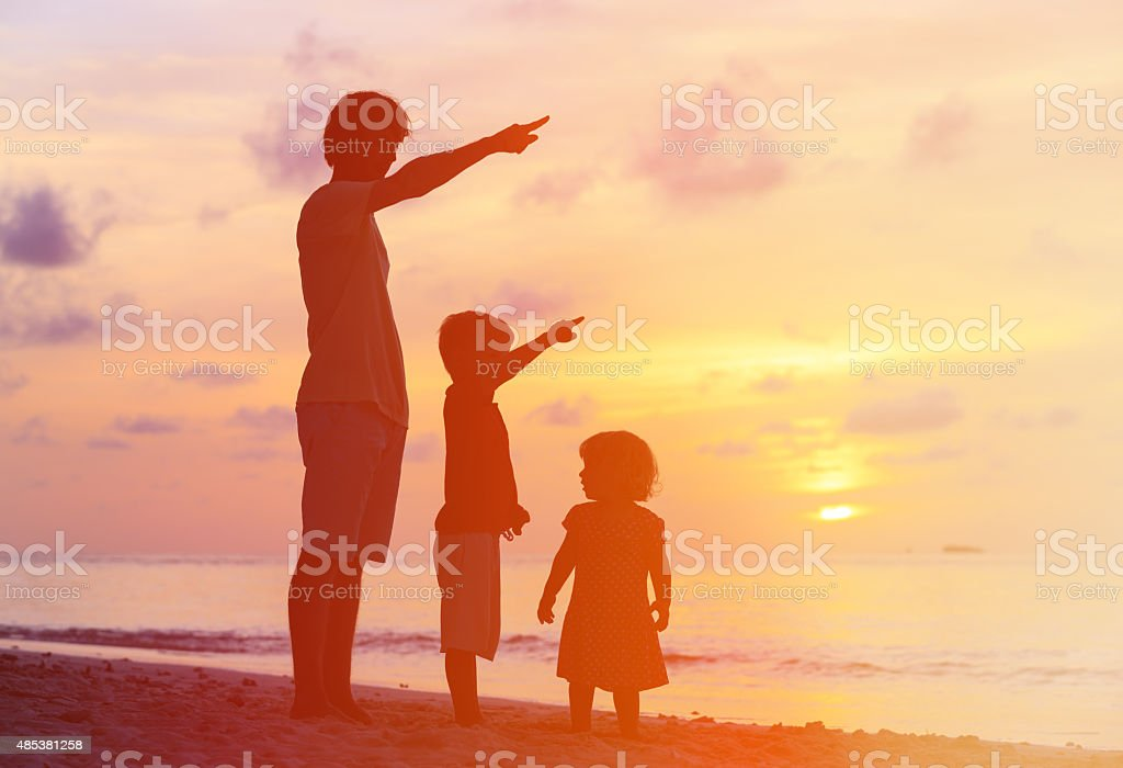 father and kids at sunset beach, pointing to the sun stock photo