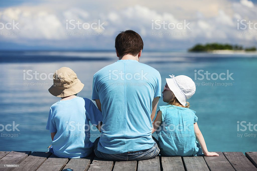 Father and kids enjoying ocean view stock photo