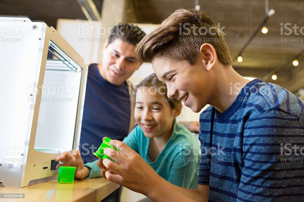 Father and kids printing 3D objects with 3D printer stock photo
