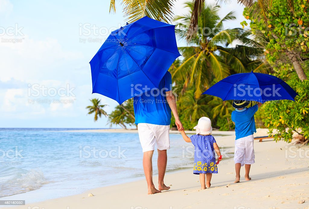 Father and kids with umbrellas to hide from sun stock photo