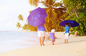 Father and kids with umbrellas to hide from sun