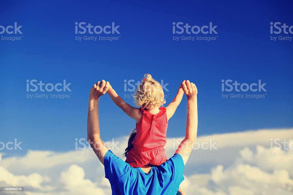 father and little daughter on shoulders play at sky stock photo