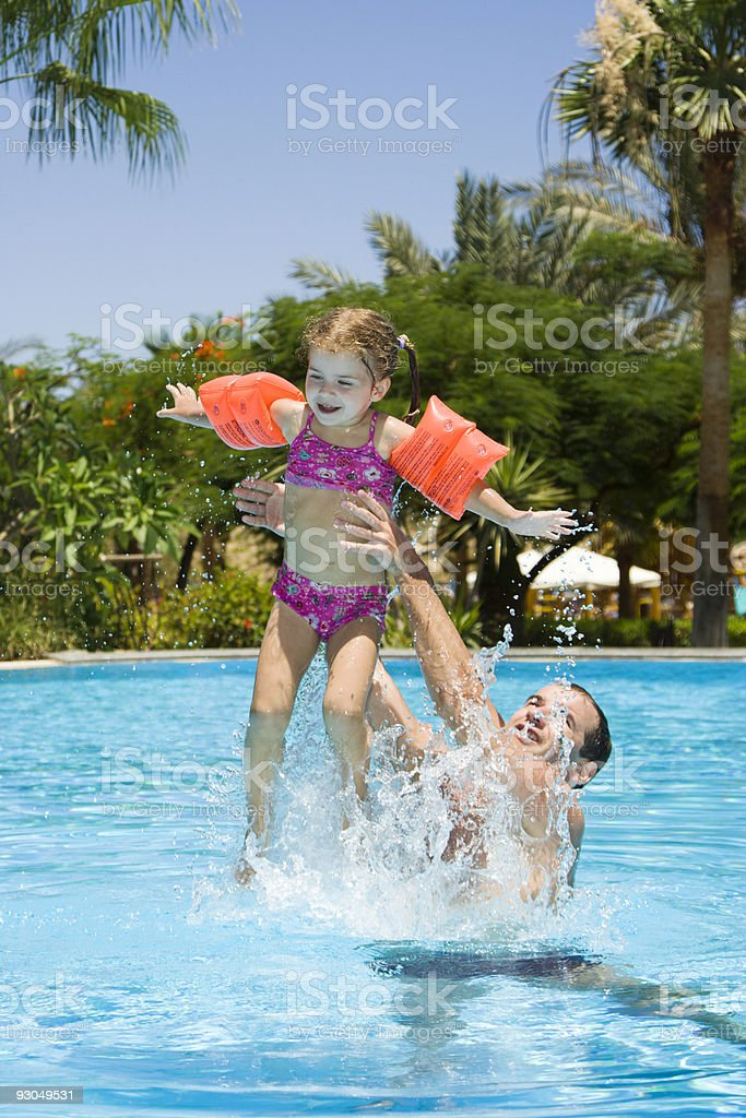 Father and little daughter playing in pool royalty-free stock photo