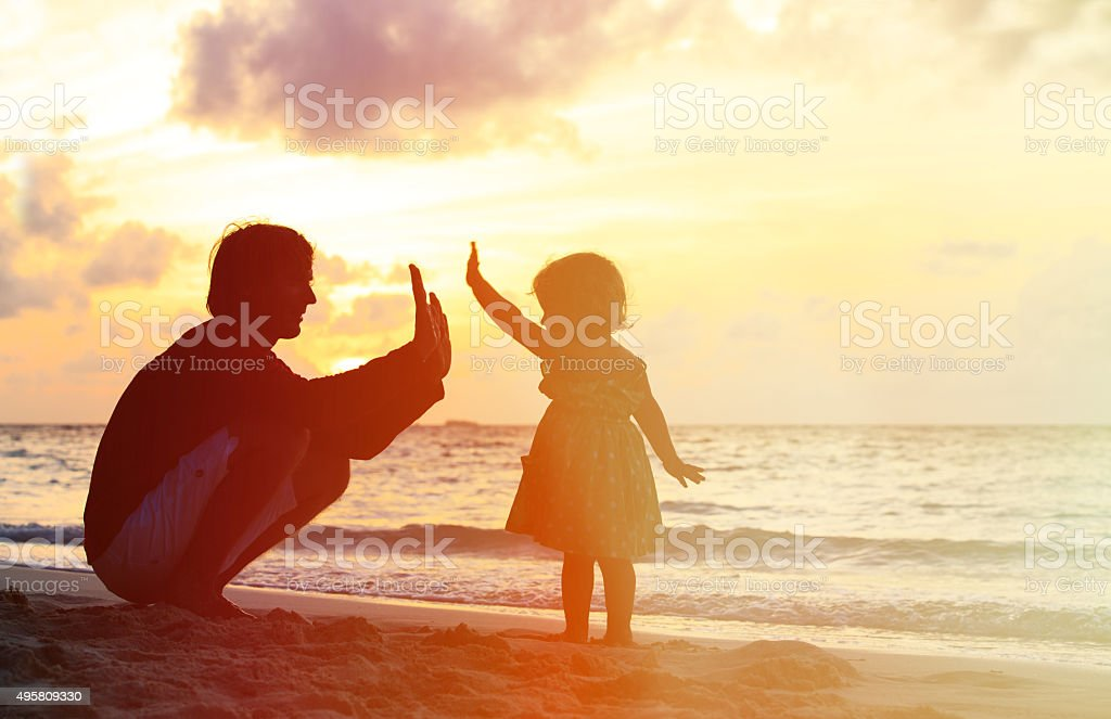 Father and little daughter playing silhouettes at sunset stock photo