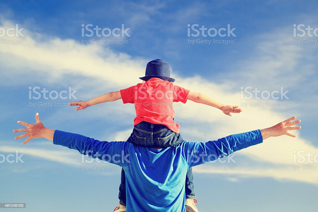 father and little son on shoulders play at sky stock photo