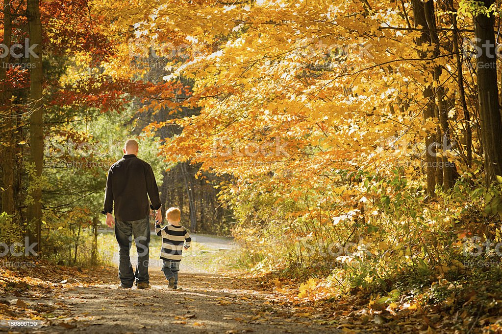 Father and Little Son Walking Outdoors in Autumn Woods stock photo