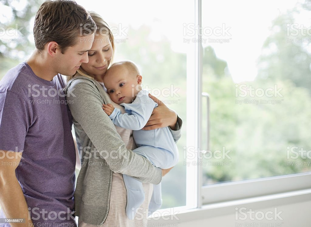 Father and mother embracing t heir baby boy (6-11 months) stock photo