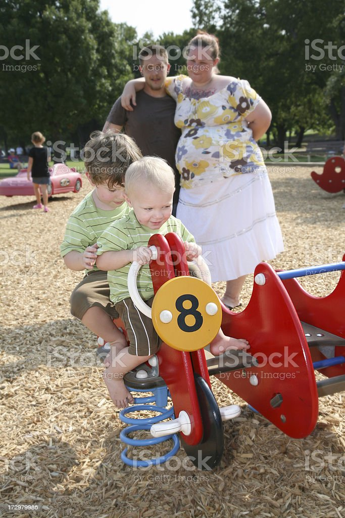 Father and Mother Watch As Sons Play At A Playgorund royalty-free stock photo