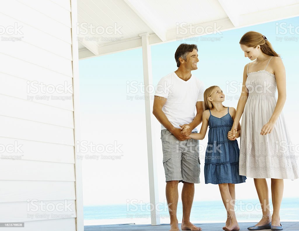 Father and mother with daughter at beach house royalty-free stock photo