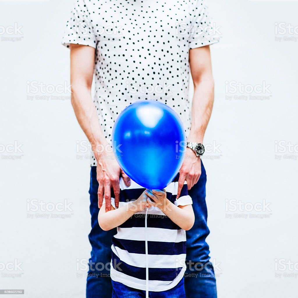 Father and shy son hiding behind a balloon stock photo