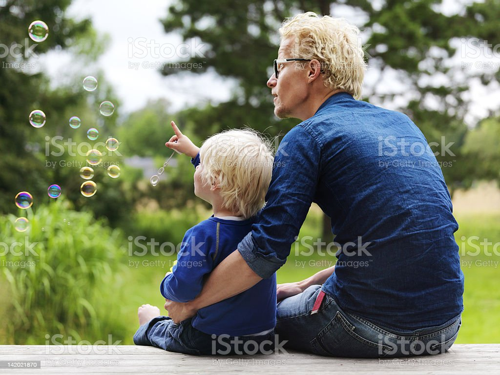 Father and son admiring bubbles outdoors stock photo
