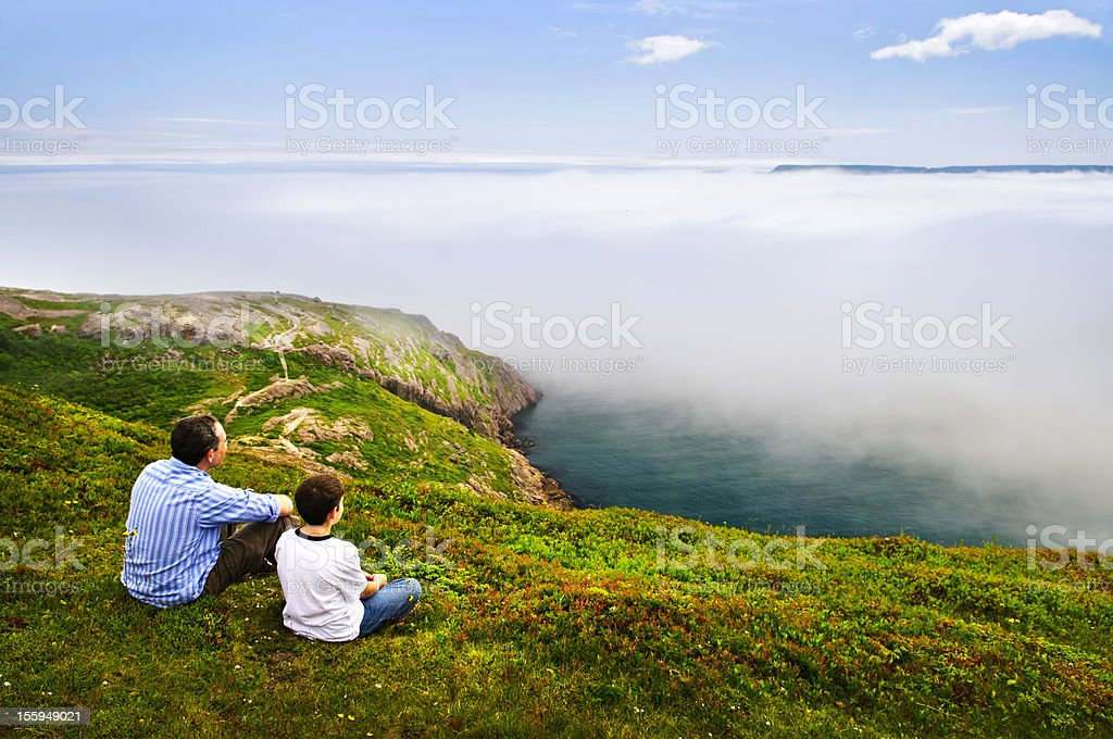 Father and son at foggy ocean coast stock photo