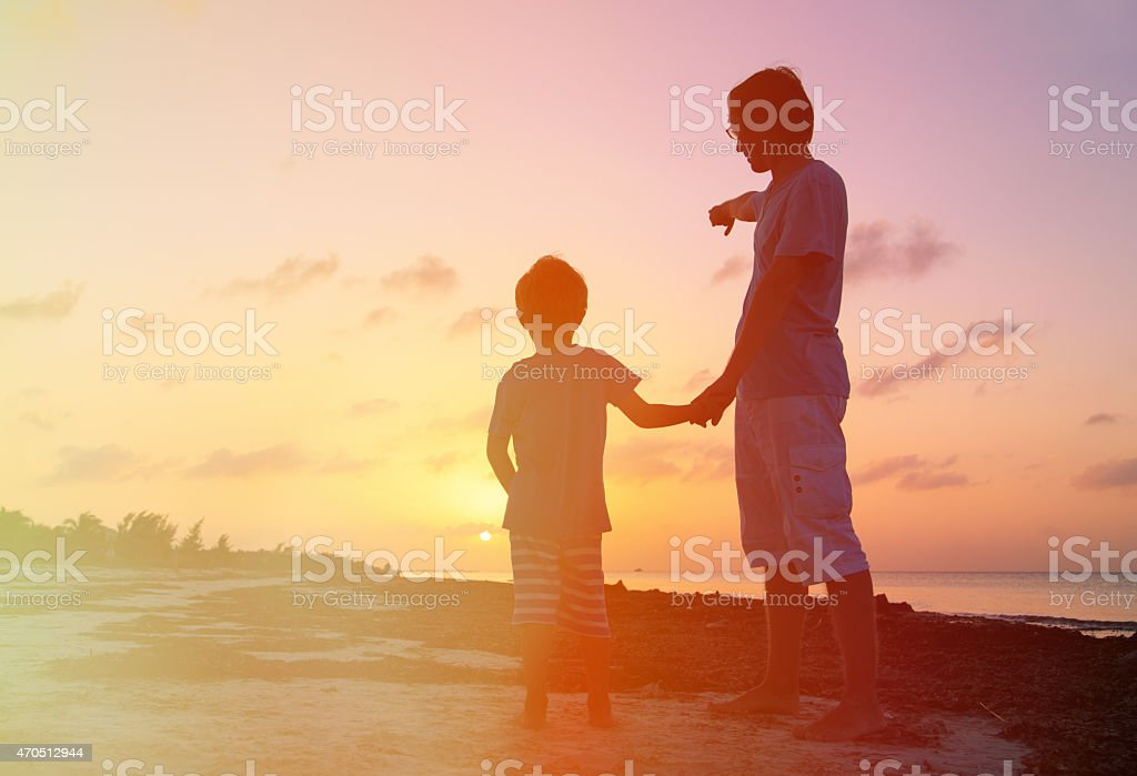father and son at sunset beach stock photo